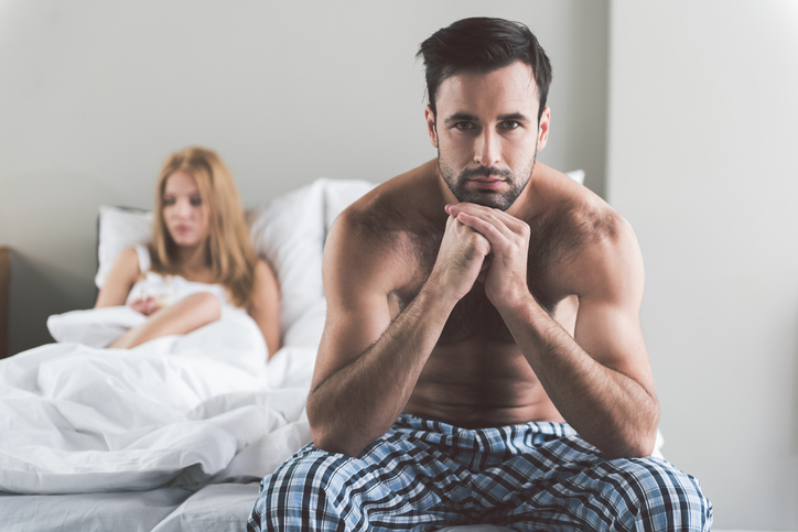 Abused young man is sitting on bedside and looking at camera with sadness. His wife is lying and expressing frustration on background. Portrait