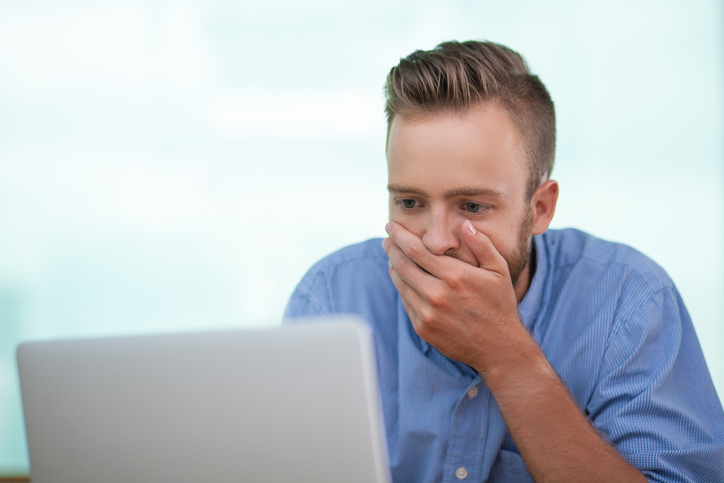 Closeup of Shocked Young Man Working on Laptop