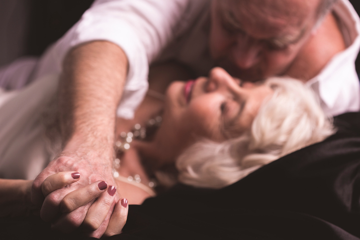 Senior man embracing mature woman, lying on bed