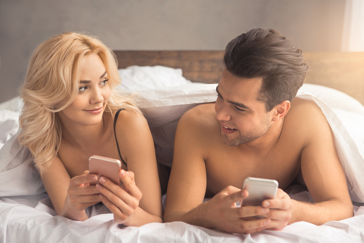Young couple man and woman intimate relationship on bed using digital devices