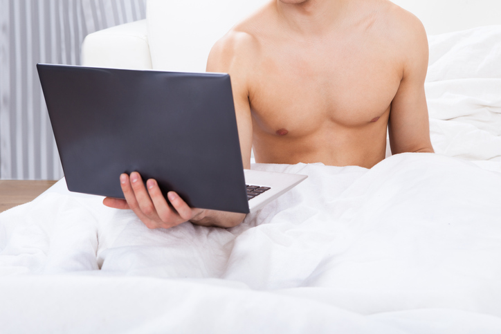 Midsection of shirtless man holding laptop in bed at home