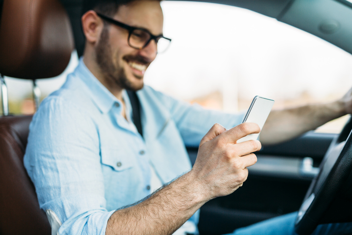 transportation concept - man using phone while driving the car