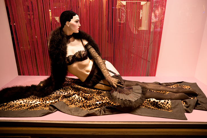 Mannequin in stockings and garter belt lying on fur in a pink window.