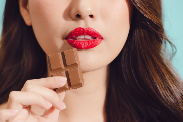 Attractive young asian woman eating chocolate, closeup