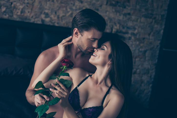 Concept of having cute gentle nice pleasant moment in personal life. Attractive charming lovely gentle woman is receiving wonderful rose from beloved careful man, they are kissing about to have sex