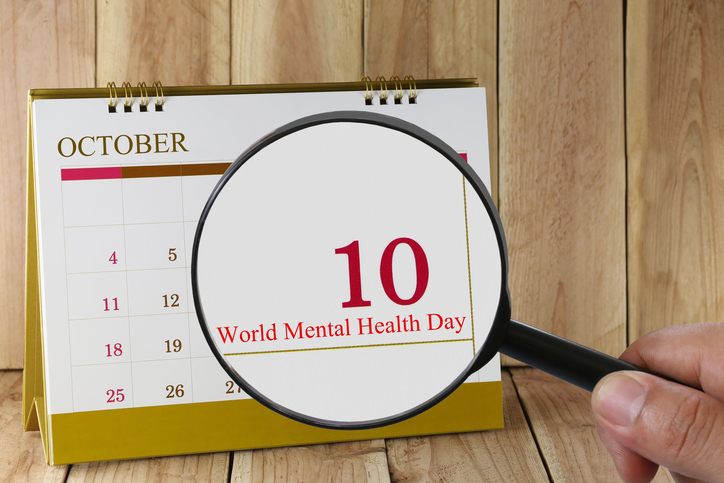 Magnifying glass in hand on calendar you can look World Mental Health Day in 10 October,concept of a public relations campaign Mental health and stress.
