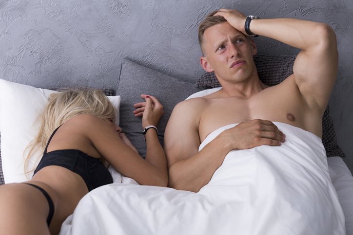 Man with a hangover lying in a hotel bed with sexy woman in a black underwear
