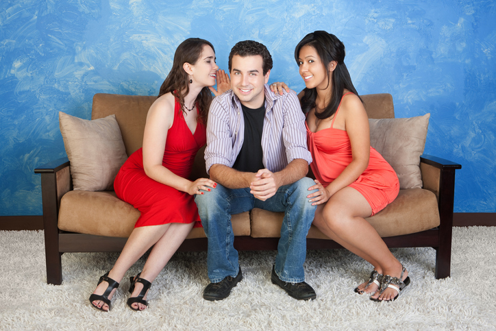 One man and two women on a couch